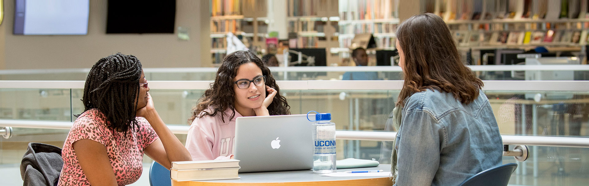 three students sitting in library talking
