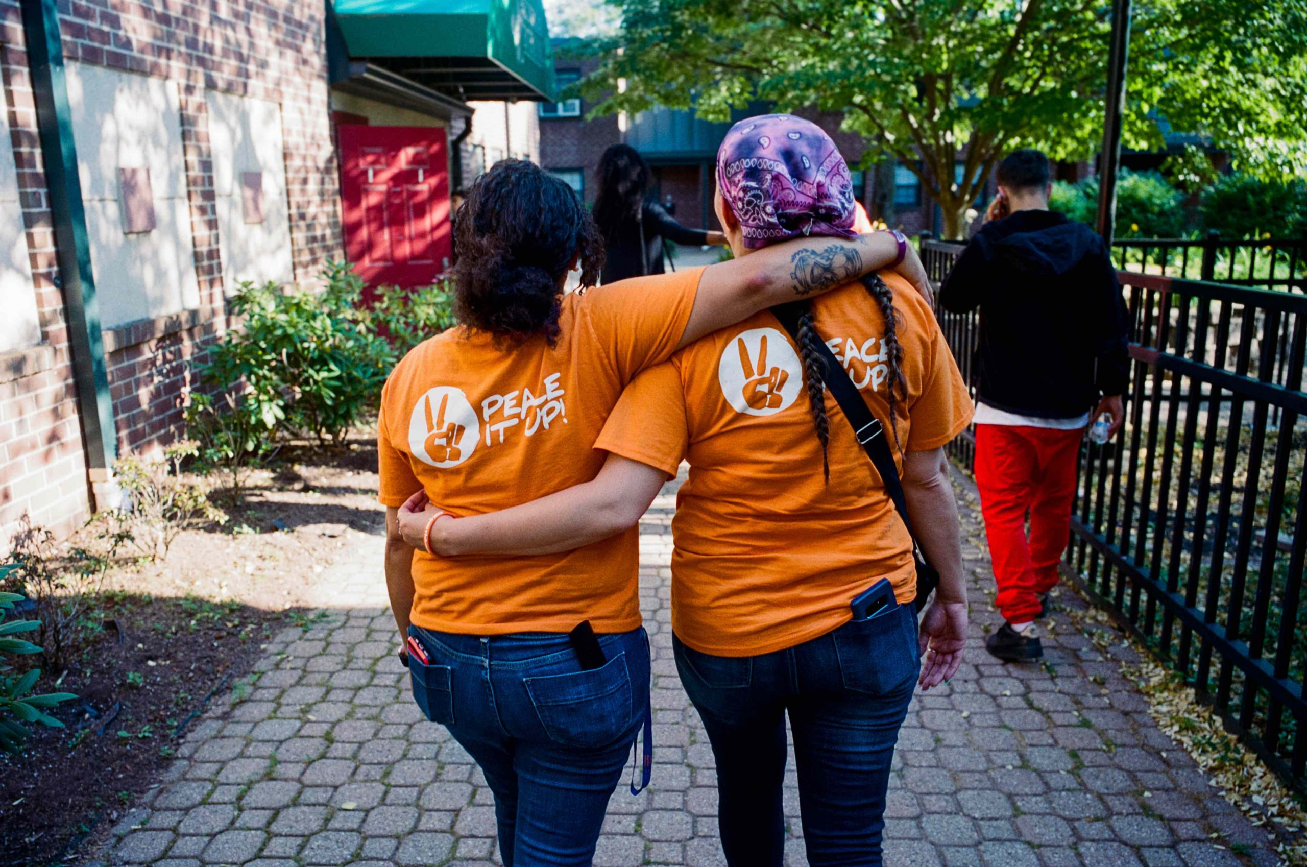 two women walking with arms around each other wearing Peace it up! shirts