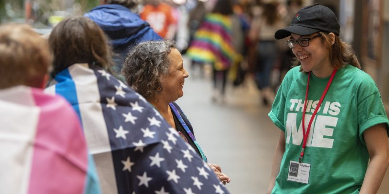 Two women smile facing each other, one wearing a This Is Me shirt as others walk by with rainbow flags